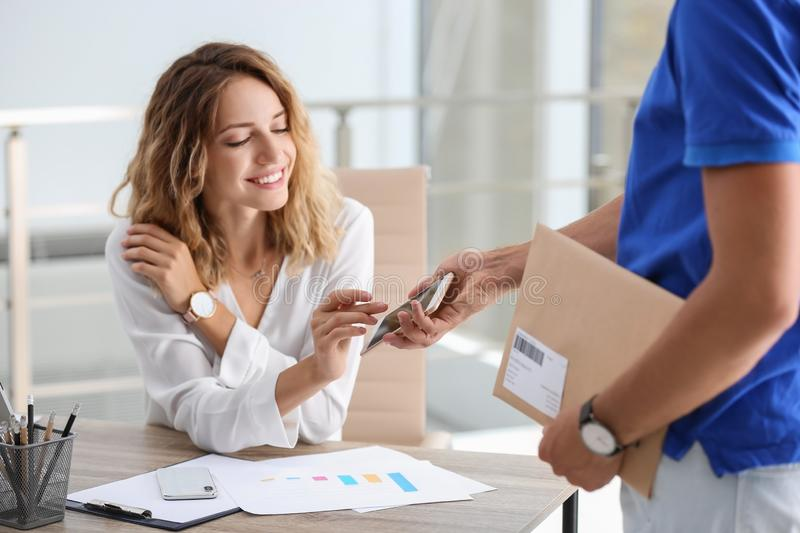 Woman using smartphone app to confirm receipt of envelope from courier. In office royalty free stock image