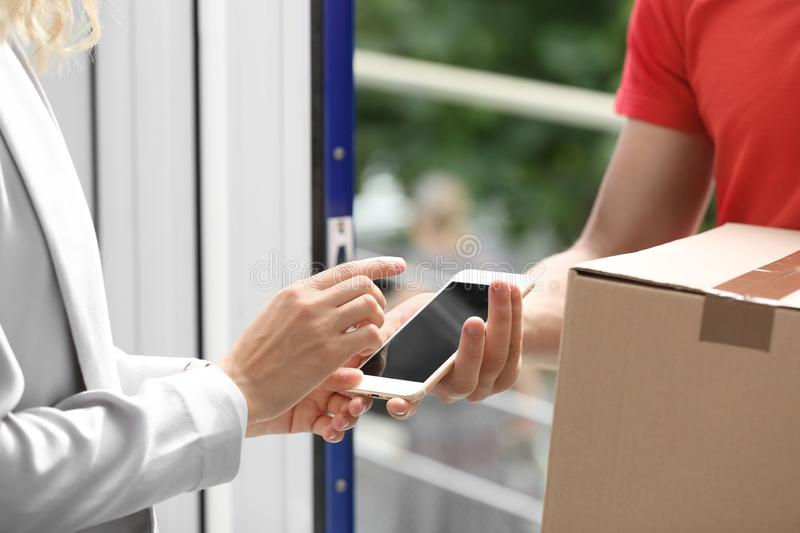 Woman using smartphone app to confirm receipt of parcel from courier. Near door stock image