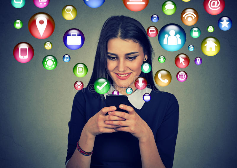 Woman using smartphone with application icons flying out of screen stock illustration