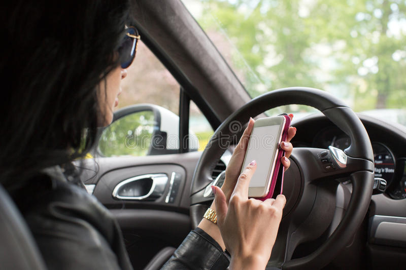 Woman using smartphone. Blurred car interior. Close up hand woman using mobile smartphone. Blurred car interior background royalty free stock photo