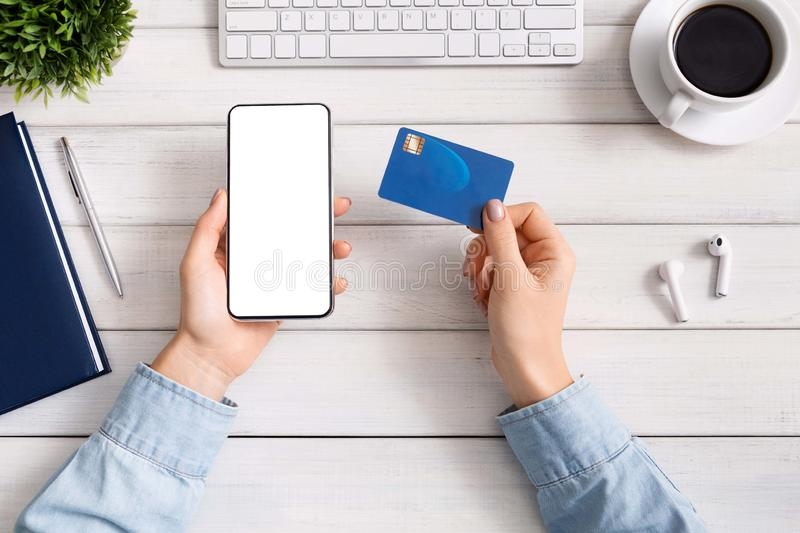 Woman using smartphone and credit card for online shopping stock images