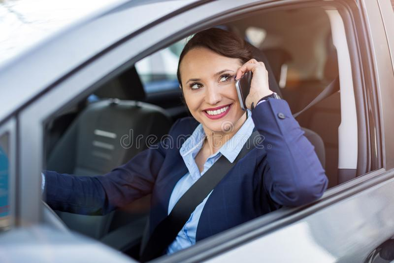 Woman using smartphone while driving a car royalty free stock photography