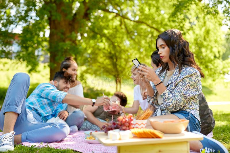 Woman using smartphone at picnic with friends stock images