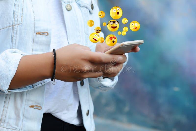 Woman using smartphone sending emojis. stock photos
