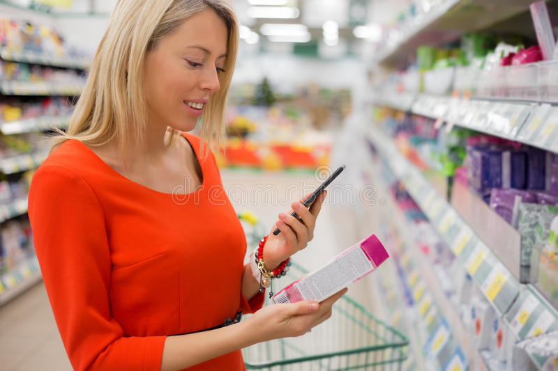 Woman using smartphone to compare prices. In supermarket royalty free stock photos