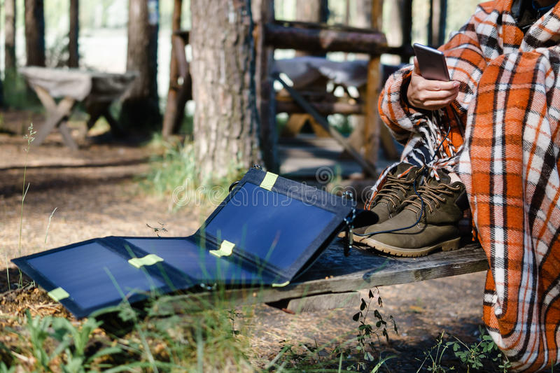 Woman using Smartphone in the woods. Charges using solar panels. royalty free stock photos