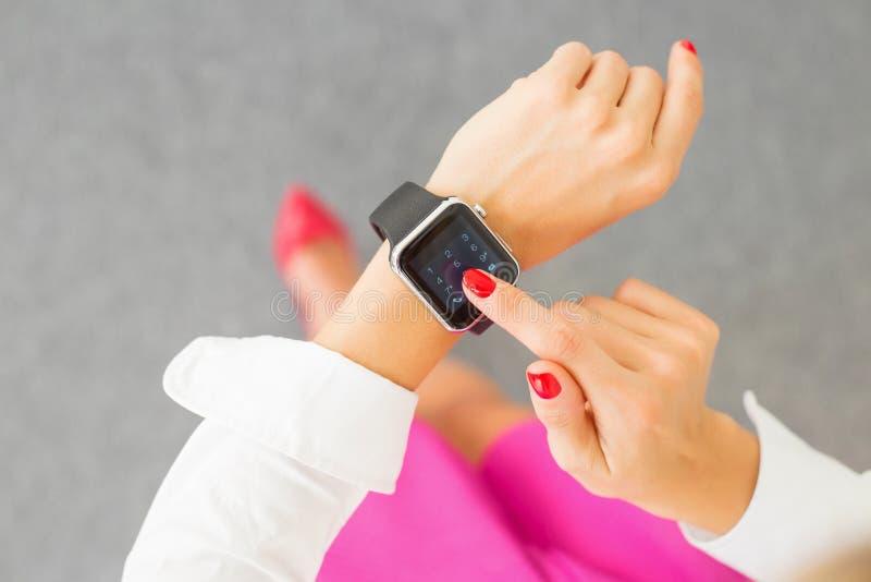Woman using smartwatch. Modern and fashionable woman using smartwatch royalty free stock photography