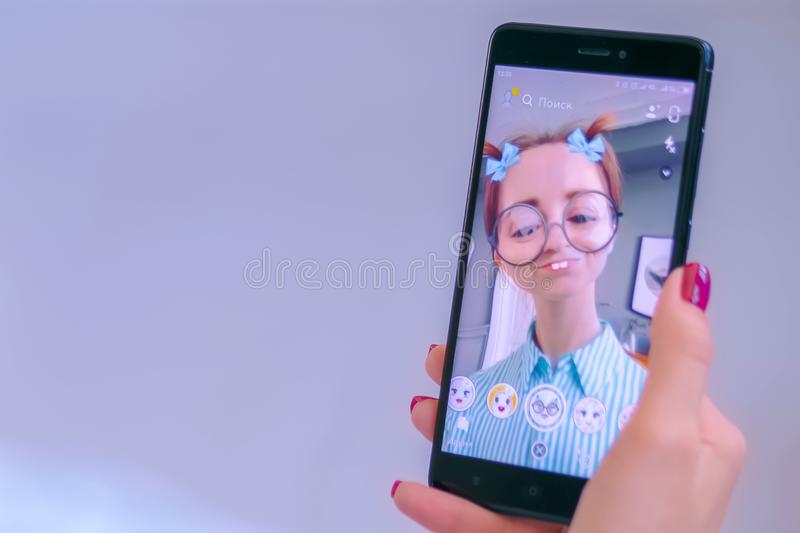 Woman using Snapchat multimedia messaging app with face mask on smartphone. MOSCOW, RUSSIA - MAY 24, 2019: Woman using Snapchat multimedia messaging app with 3d stock photos