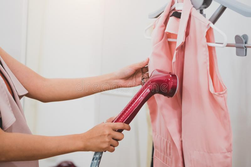 Woman using steaming iron to ironing fashion shirt in laundry room. Girl doing stream vapor iron for press clothes in hand. stock image