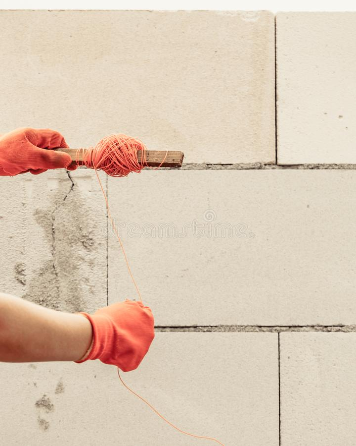 Woman using string as level in wall construction stock photo