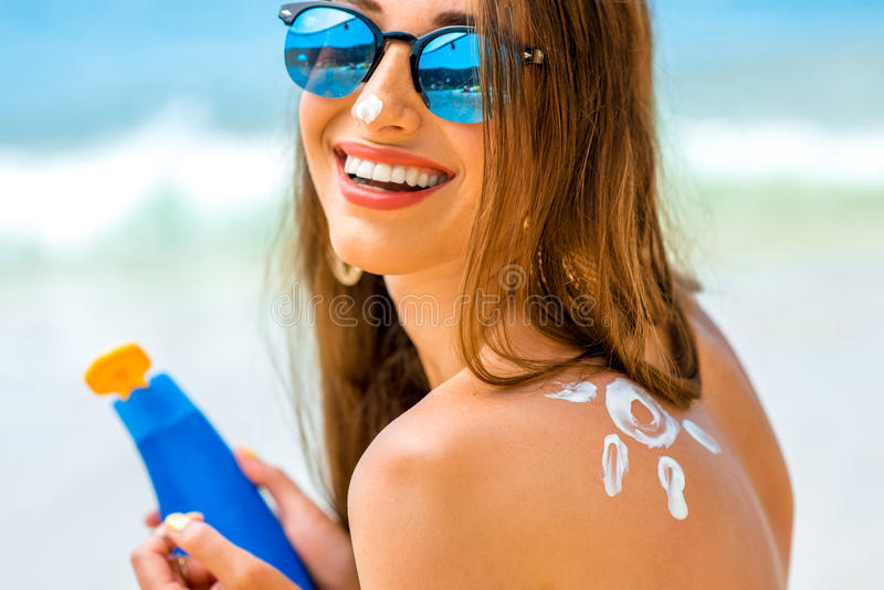 Woman using sun cream on the beach. Young woman with sun shape on the shoulder holding sun cream bottle on the beach royalty free stock images