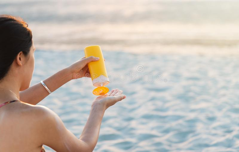 Woman using sun lotion on the beach. Woman using sun lotion on beach summer vacation, protection, girl, apply, shoulder, sunbathing, sunscreen, applying, spf royalty free stock photo