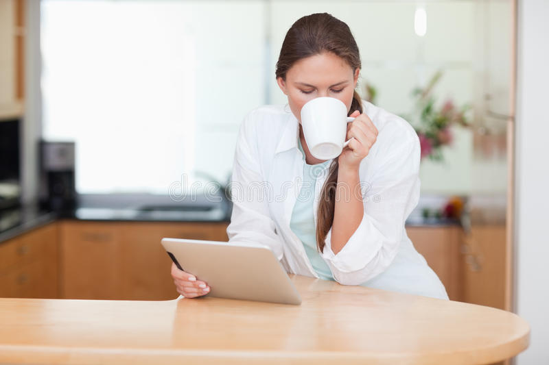 Woman Using A Tablet Computer While Drinking Coffee Stock Photos