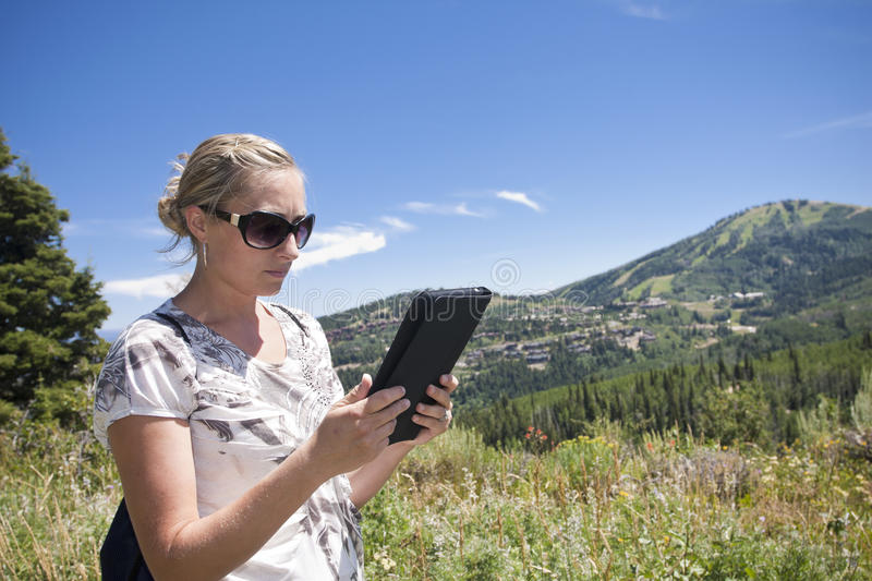 Woman using tablet computer outdoors. A woman using her tablet computer while hiking in the mountains royalty free stock image