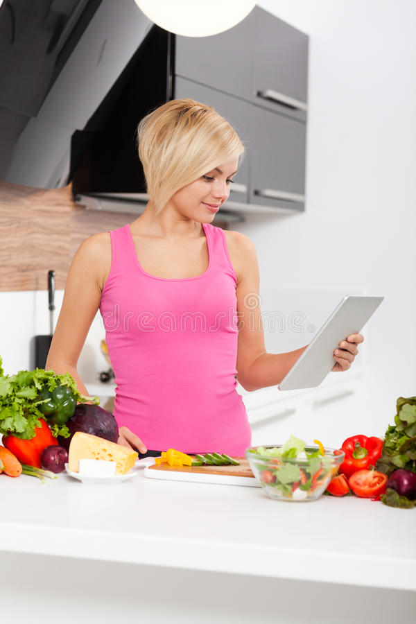Woman using a tablet computer to cook. Blonde woman using a tablet computer to cook in modern kitchen, young girl fresh raw vegetables cooking at home smile stock images