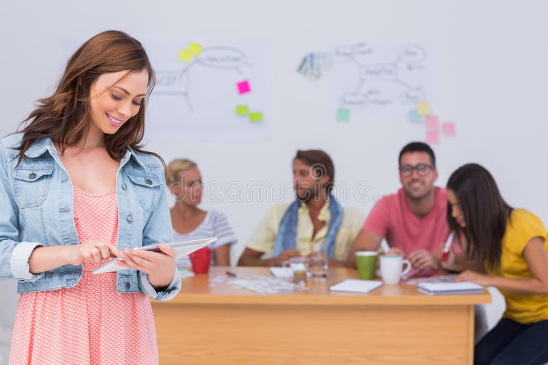 Woman using tablet with creative team working behind her stock images
