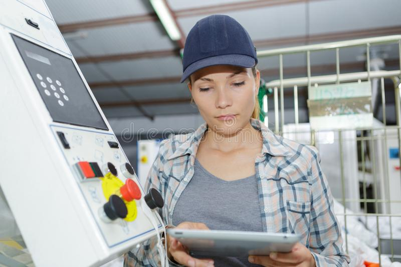 Woman using tablet next to machinery controls royalty free stock photos