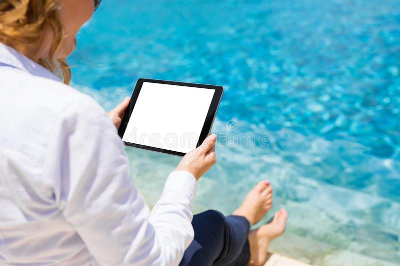 Woman using tablet by the pool stock photos