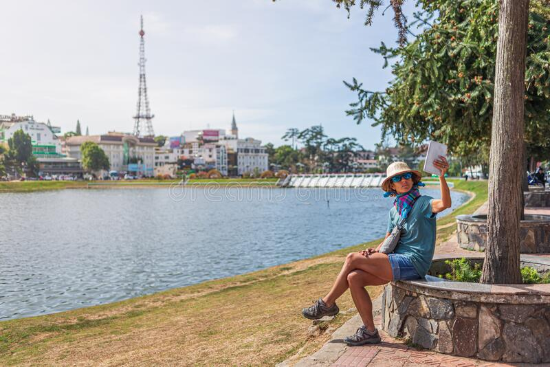 Woman using tablet smart phone in green city park lake at Da Lat town, Vietnam. Lady with vietnamese hat taking selfie having fun stock photography