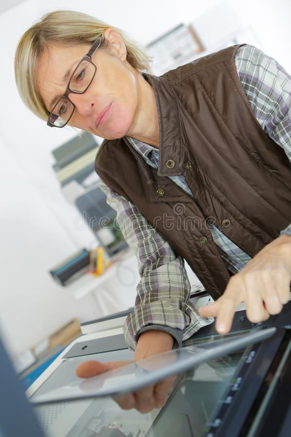Woman using tablet to aid repair photocopier stock photography