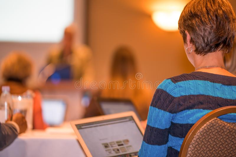 Woman using technology to help take in information while watching a keynote speaker at a conference with a slide deck presentation royalty free stock photo