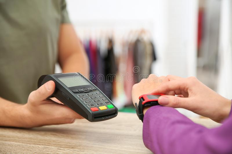 Woman using terminal for contactless payment with smart watch in shop. Closeup royalty free stock photography