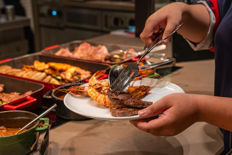 Woman using tongs picking delicious grilled shrimps at seafood restaurant. Woman using tongs picking delicious grilled shrimps at buffet restaurant royalty free stock photography
