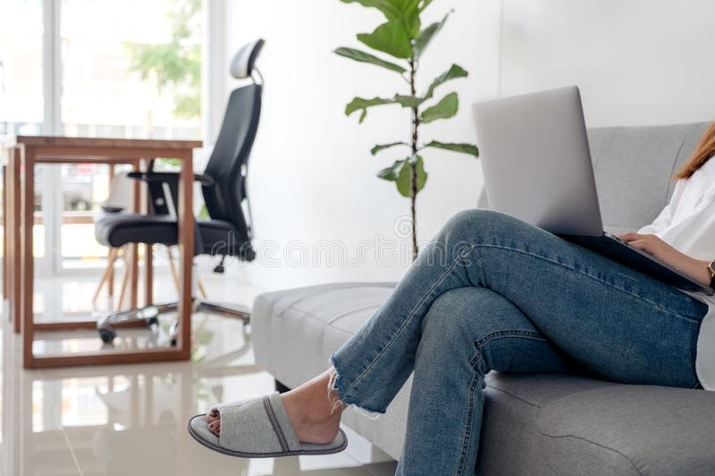 Woman using and typing on laptop keyboard while sitting on sofa with feeling relaxed stock photos