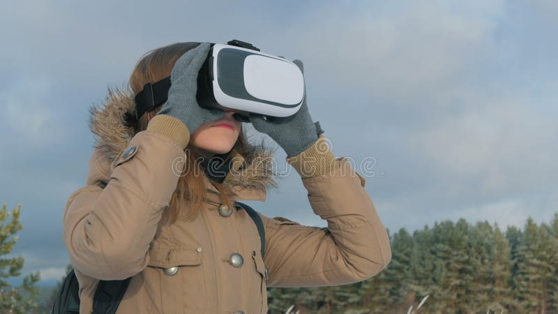 Woman using virtual reality glasses in winter forest. Woman putting on and using virtual reality glasses in winter forest. Virtual reality mask. VR. Future stock images
