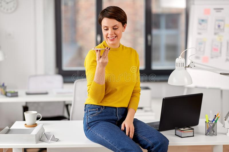 Woman using voice recorder on smartphone at office. Business, technology and people concept - happy smiling businesswoman using voice command recorder on royalty free stock photos