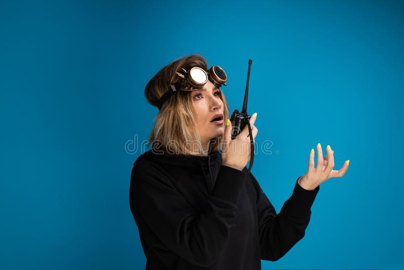Woman using walkie talkie to communicate while wearing steam punk glasses on her head royalty free stock photo