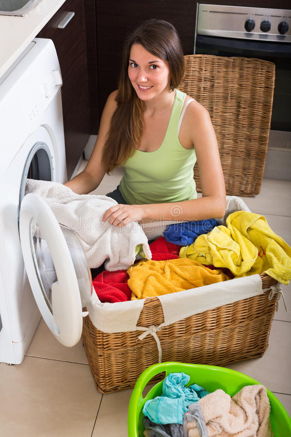 Woman using washing machine royalty free stock photography