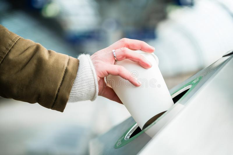 Woman using waste separation container throwing away coffee cup royalty free stock photos