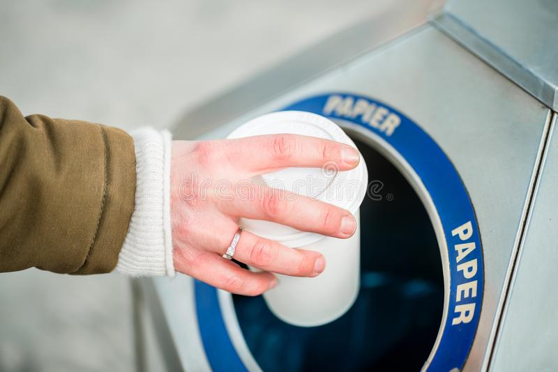 Woman using waste separation container throwing away coffee cup stock images