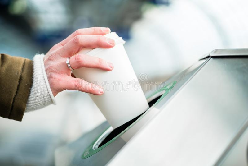 Woman using waste separation container throwing away coffee cup stock photo