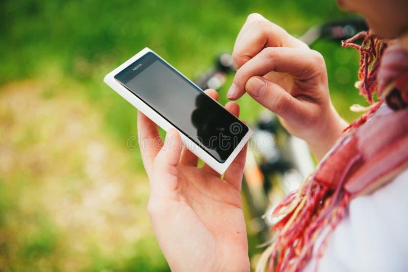 Woman using white Nokia Lumia white smartphone royalty free stock images