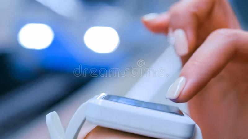 Woman using white smart watch on subway platform. Woman hands using white wearable smartwatch computer device on subway platform. Train arriving at station royalty free stock photos