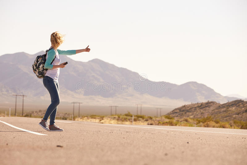 Woman On Vacation Hitchhiking Along Country Road stock photography