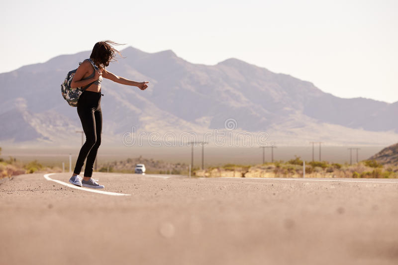 Woman On Vacation Hitchhiking Along Country Road royalty free stock image