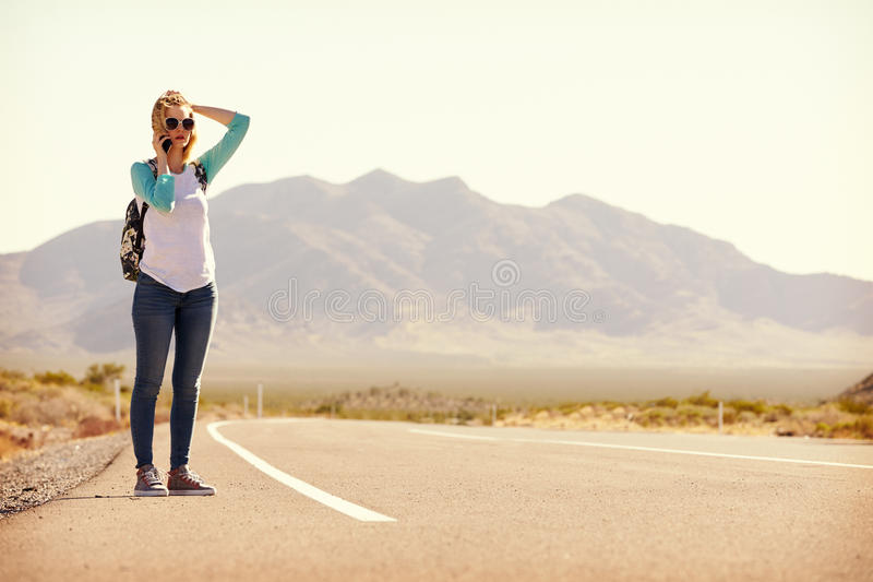Woman On Vacation Hitchhiking Along Road Using Mobile Phone stock photos