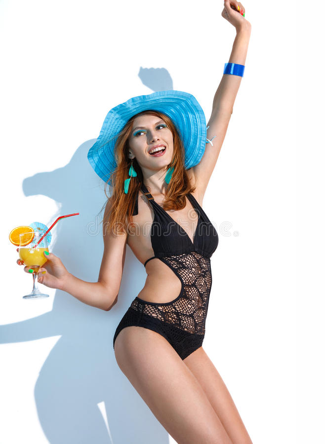 Woman on vacation. Photography of dancing woman wearing swimsuit with refreshing summer drink in her hand on white background stock image