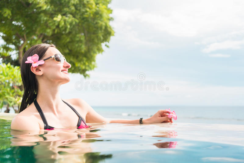 Woman in vacation relaxing swimming in pool royalty free stock image
