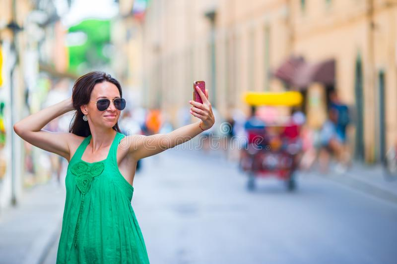 Woman on vacation travel. Smiling happy caucasian girl having fun laughing during holidays in Rome, Italy, Europe. Woman taking selfie on vacation travel in old stock photography