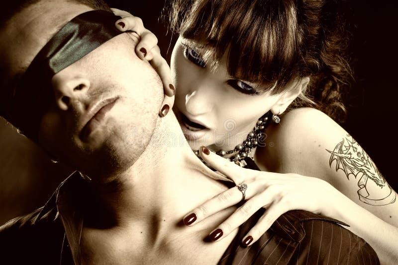 Woman vampire bites a blind man stock photos