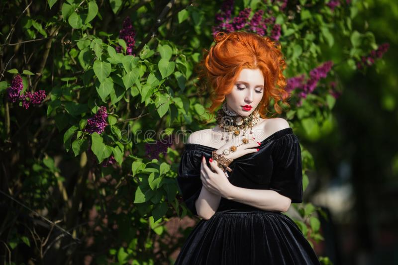 A woman is a vampire with pale skin and red hair in a black dress and a necklace royalty free stock photos