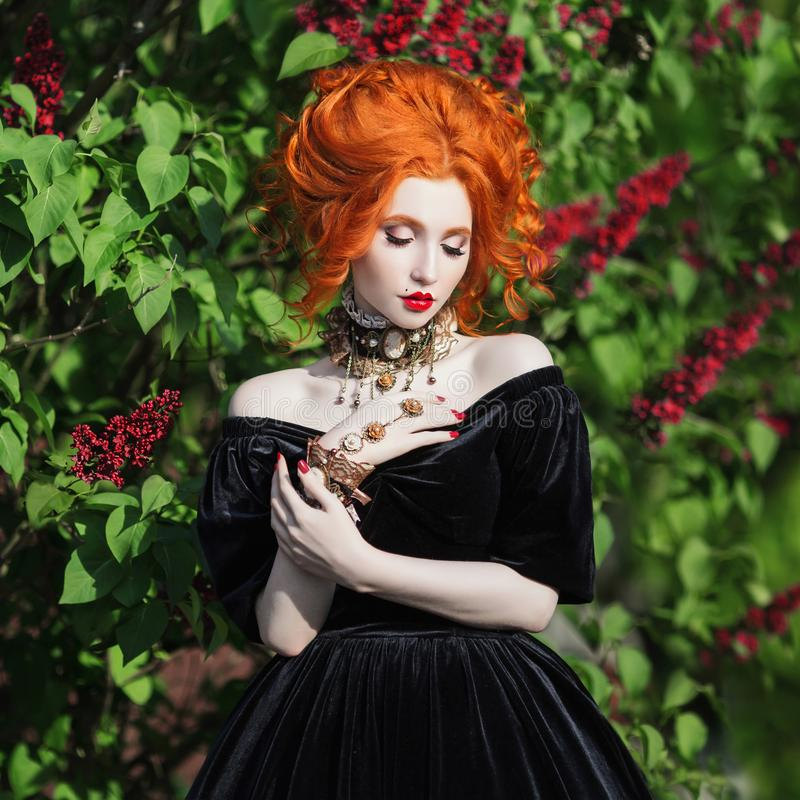 A woman is a vampire with pale skin and red hair in a black dress and a necklace royalty free stock image