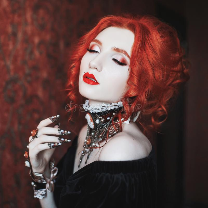 A woman is a vampire with pale skin and red hair in a black dress and a necklace on her neck. Girl witch with vampire claws. And red lips. Gothic look. Outfit royalty free stock images