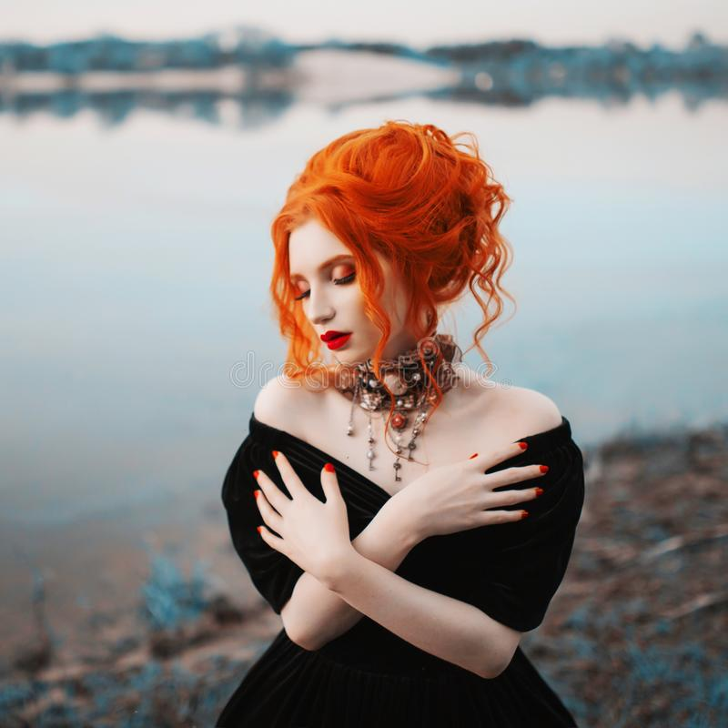 A woman is a vampire with pale skin and red hair in a black gothic dress and a necklace on her neck. stock images