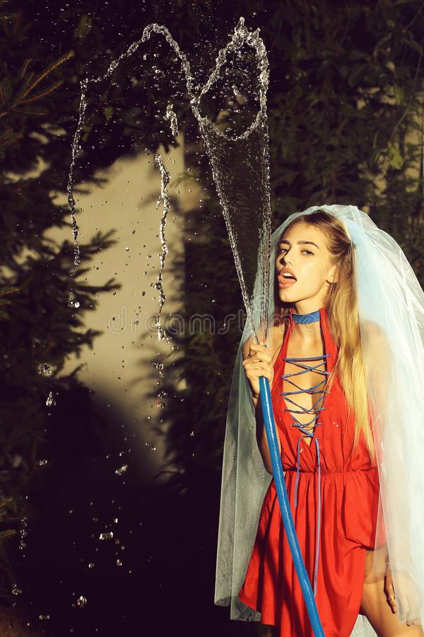 Woman in veil with hose and water. Young woman bride with pretty face and long blonde hair, in red dress and blue veil holding hose with water drops outdoor in stock photography