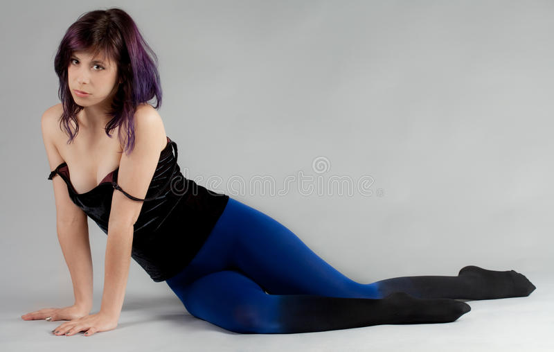 Woman in Velvet Top and Ombre Stockings. An image of a pretty seated young woman in a black velvet top and blue to black ombre tights royalty free stock photos